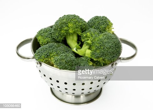 Colander filled with fresh broccoli. : Stock Photo