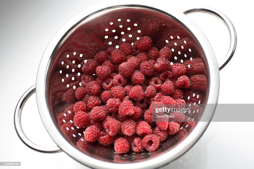 A colander full of raspberries on white. : Stock Photo