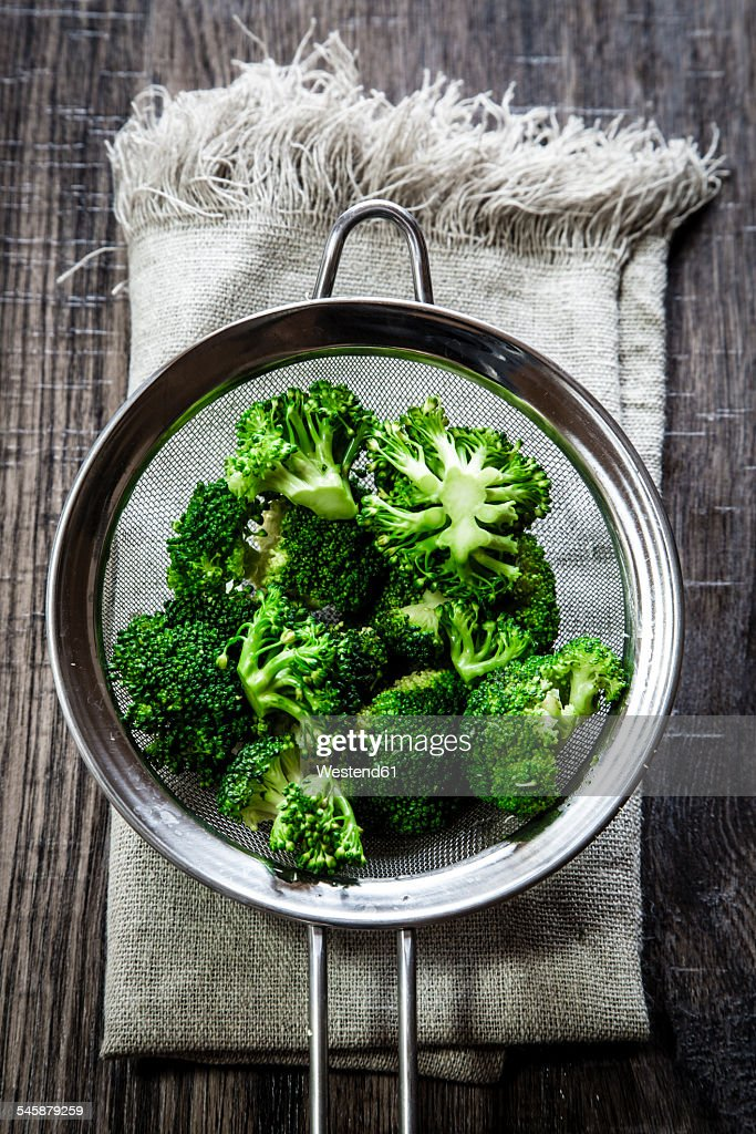 Colander of broccoli florets on cloth and wood