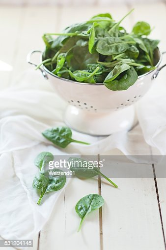 Colander of fresh spinach leaves on white cloth and wood