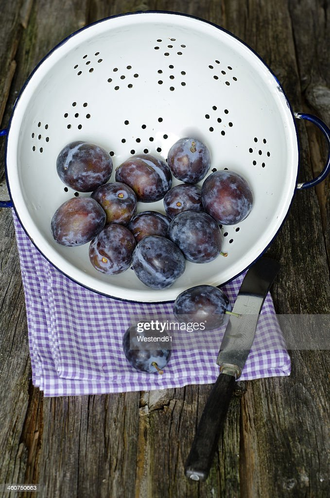Colander of prunes with napkin on wooden table, close up