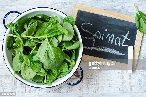 Colander of spinach leaves and chalkboard