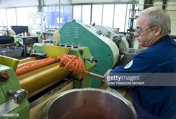 A Colart company's worker displays paint in a rolling mill to crush pigments on december 13 in Le Mans western France Since 1988 the Colart company...