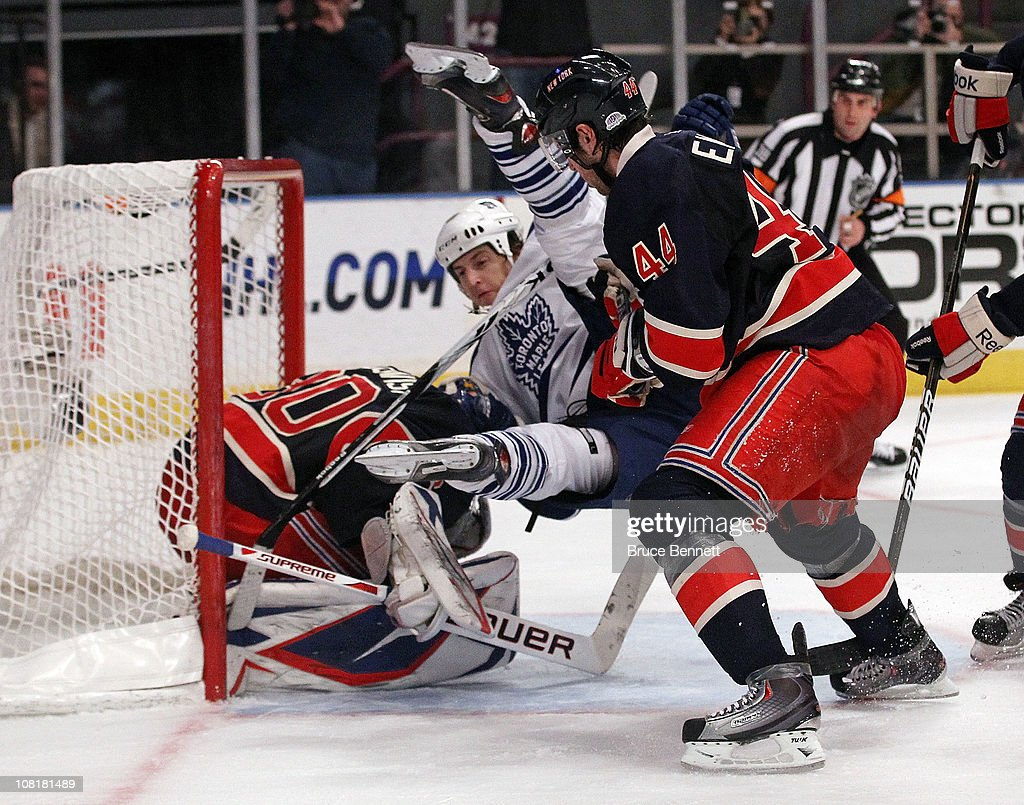 Colby Armstrong of the Toronto Maple Leafs is flipped in the crease by Steve Eminger of the New York Rangers in front of goaltender Henrik Lundqvist...