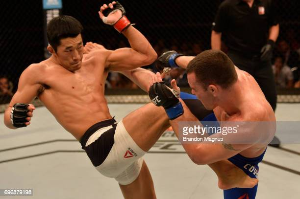 Colby Covington and Dong Hyun Kim of South Korea trade kicks in their welterweight bout during the UFC Fight Night event at the Singapore Indoor...