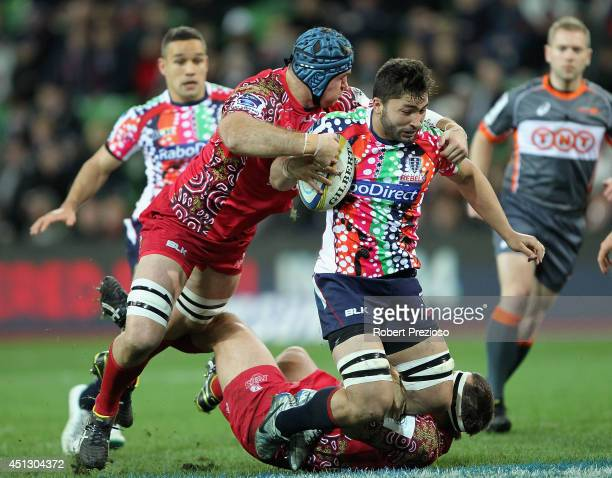 Colby Fainga'a of the Rebels is tackled by James Horwill of the Reds during the round 17 Super Rugby match between the Rebels and the Reds at AAMI...
