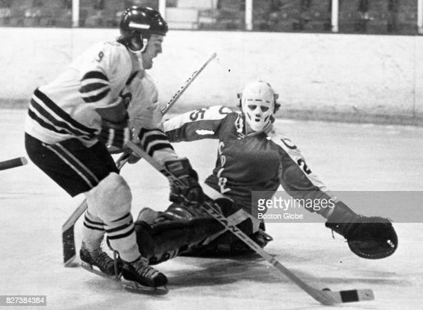 Colby goaltender Frank Evans reaches out to make a save on Northeastern University's Charlie Huck during a game at Boston Arena on Feb 8 1975