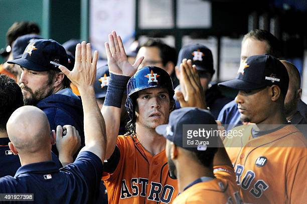 Colby Rasmus of the Houston Astros celebrates with teammates in the dugout after driving in a run in the first inning during game one of the American...