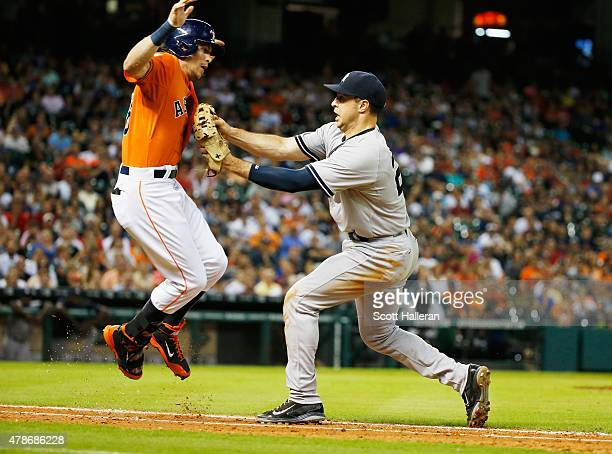 Colby Rasmus of the Houston Astros is tagged out at first base by Mark Teixeira of the New York Yankees in the ninth inning of their game at Minute...