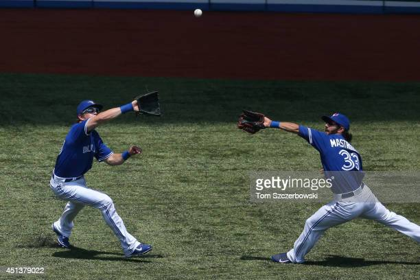 Colby Rasmus of the Toronto Blue Jays catches a fly ball while nearly colliding with Darin Mastroianni in the first inning during MLB game action...