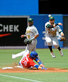 Colby Rasmus of the Toronto Blue Jays is forced out at second base as Eric Sogard of the Oakland Athletics throws on to first in the second inning of...