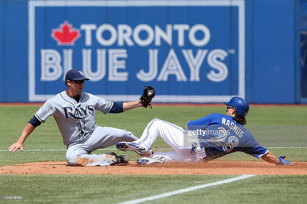 Colby Rasmus #28 of the Toronto Blue Jays is forced out at second base in the second inning during MLB game action as Kelly Johnson #2 of the Tampa Bay Rays falls after making the putout on July 21, 2013 at Rogers Centre in Toronto, Ontario, Canada.