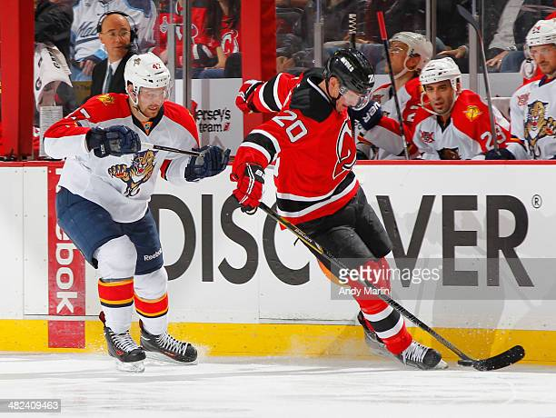 Colby Robak of the Florida Panthers and Ryan Carter of the New Jersey Devils battle for position on a loose puck during the game at the Prudential...
