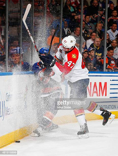 Colby Robak of the Florida Panthers checks Anders Lee of the New York Islanders at Nassau Veterans Memorial Coliseum on April 1 2014 in Uniondale New...
