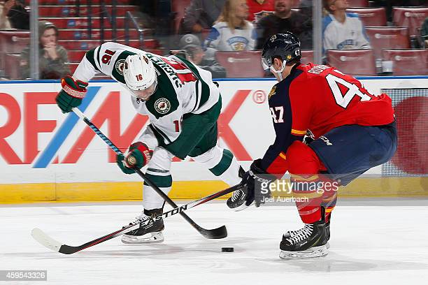 Colby Robak of the Florida Panthers defends against Jason Zucker of the Minnesota Wild as he shoots the puck at the BBT Center on November 24 2014 in...
