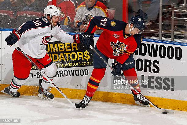 Colby Robak of the Florida Panthers digs the puck out from the boards against Boone Jenner of the Columbus Blue Jackets at the BBT Center on April 12...