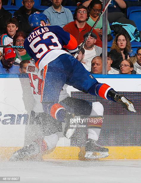 Colby Robak of the Florida Panthers is checked into the boards by Casey Cizikas of the New York Islanders at Nassau Veterans Memorial Coliseum on...