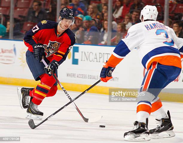 Colby Robak of the Florida Panthers skates with the puck against Travis Hamonic of the New York Islanders at the BBT Center on November 14 2014 in...
