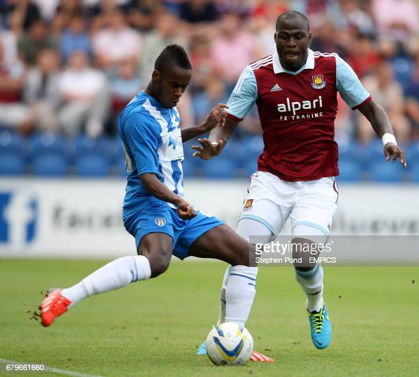 Colchester United's Gavin Massey and West Ham United's Guy Demel battle for the ball