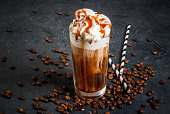 Cold coffee drink frappe with whipped cream and caramel syrup, with straws and grains of coffee on a dark gray stone table, copy space