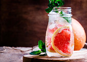 Cold drink with grapefruit and soda, mint and ice in a glass bottle, vintage wooden background, selective focus