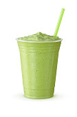 A green tea frappe or milkshake with a straw. This blended drink is made with Japanese matcha powder, ice, sugar, and regular or non-dairy milk in a plastic cup on a white background.