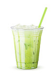 A cold iced green tea latte in a generic plastic cup with a green straw isolated on a white background. Milk (or a non-dairy milk like coconut or soy) is poured over sweetened matcha (green tea) and i