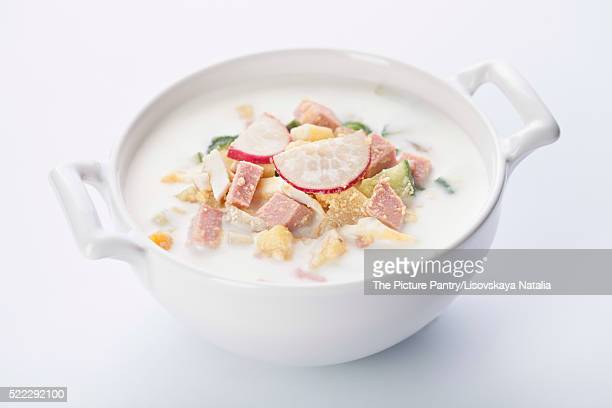 Cold kefir soup with eggs and sausage on white background