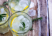 Cold lemon drink with rosemary, ice and tonic, on rustic wooden table. Selective focus