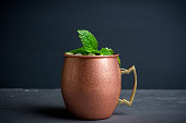 Cold Moscow Mule cocktail in copper mug on the rustic background. Shallow depth of field.