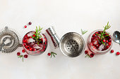 Cold refreshing drink with cranberries and rosemary on a white concrete background, top view, copy space