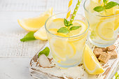 Cold refreshing summer drink with lemon and mint on wooden background, selective focus