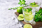 Cold refreshing summer lemonade mojito in a glass on a grey concrete or stone background.
