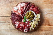 Cold smoked meat plate with prosciutto, salami, bacon, cheese and olives on wooden background. From top view