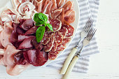 Cold smoked meat plate with pork, prosciutto, salami and bresaola on white wooden background. Wine appetizer set. Italian food. Top view.