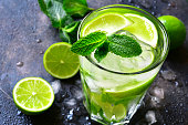 Cold summer drink mojito in a tall glass on a dark slate,stone or metal background.
