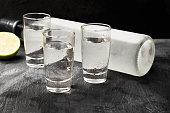 Cold vodka in shot glasses on a black background