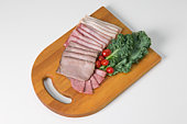 Cold-cuts, lettuce and cherry tomatoes on wooden cutting board