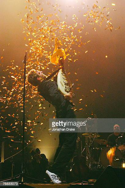 Coldplay lead singer Chris Martin bursts a balloon with his guitar at the Singapore Indoor Stadium in Singapore Singapore