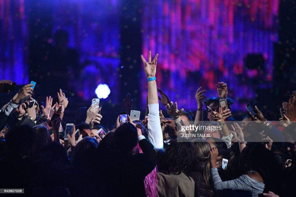 TOPSHOT - Coldplay's Chris Martin jumps into the crowd as he performs with The Chainsmokers during the BRIT Awards 2017 ceremony and live show in London on February 22, 2017. / AFP PHOTO / Justin TALLIS / RESTRICTED