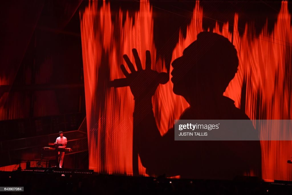 TOPSHOT - Coldplay's Chris Martin performs with The Chainsmokers during the BRIT Awards 2017 ceremony and live show in London on February 22, 2017. / AFP PHOTO / Justin TALLIS / RESTRICTED