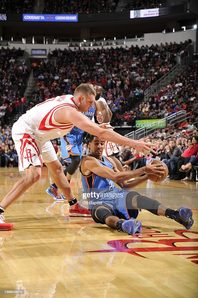 Cole Aldrich #31 of the Houston Rockets and Thabo Sefolosha #2 of the Oklahoma City Thunder battle for the ball on December 29, 2012 at the Toyota Center in Houston, Texas.