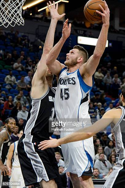 Cole Aldrich of the Minnesota Timberwolves shoots the ball against Pau Gasol and Nicolas Laprovittola of the San Antonio Spurs during the game on...