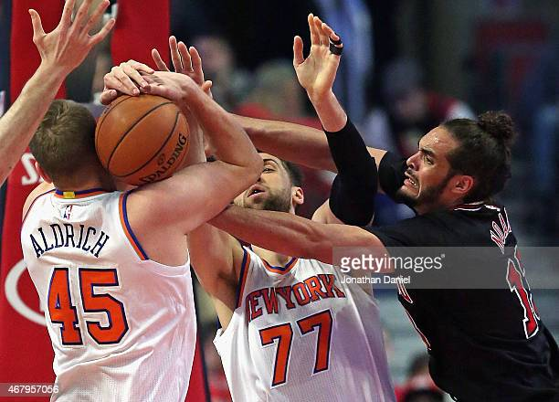 Cole Aldrich of the New York Knicks fights to keep the ball from teammate Andrea Bargnani and Joakim Noah of the Chicago Bulls at the United Center...