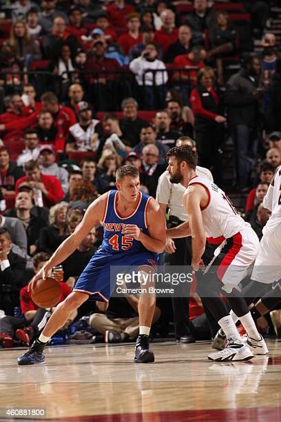 Cole Aldrich of the New York Knicks handles the ball against Joel Freeland of the Portland Trail Blazers on December 328 2014 at the Moda Center in...