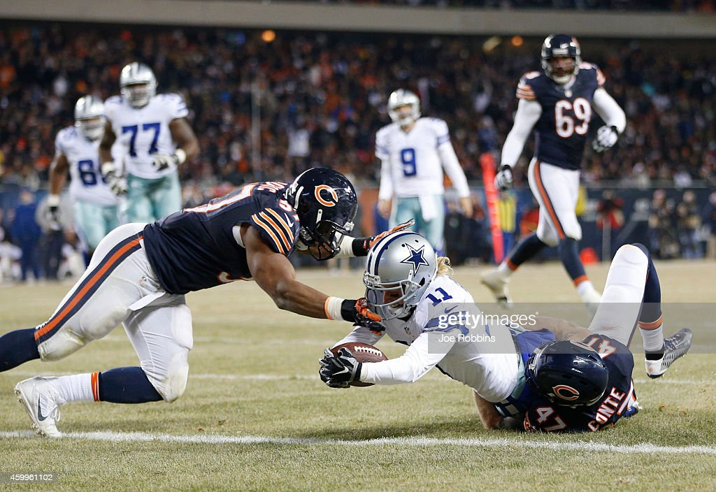 Cole Beasley #11 of the Dallas Cowboys drives through Chris Conte #47 and Jon Bostic #57 of the Chicago Bears for a touchdown during the second quarter of a game at Soldier Field on December 4, 2014 in Chicago, Illinois.