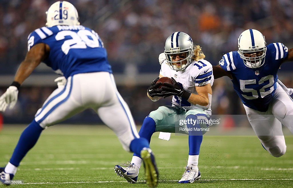Cole Beasley #11 of the Dallas Cowboys eludes D'Qwell Jackson #52 of the Indianapolis Colts and Mike Adams #29 of the Indianapolis Colts to score a touchdown in the first half at AT&T Stadium on December 21, 2014 in Arlington, Texas.