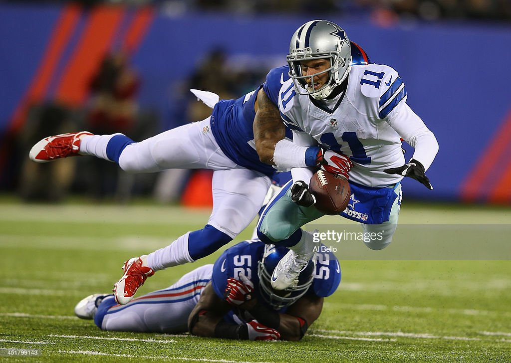 Cole Beasley of the Dallas Cowboys is tackled against Terrell Thomas and Jon Beason of the New York Giants during their game at MetLife Stadium on...