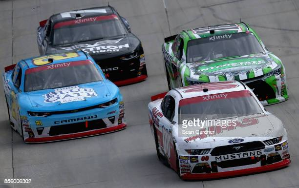 Cole Custer driver of the Haas Automation Ford leads Daniel Hemric driver of the Blue Gate Bank Chevrolet Daniel Suarez driver of the Interstate...