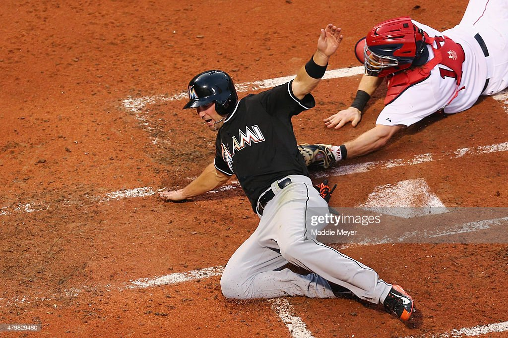 Cole Gillespie #28 of the Miami Marlins scores a run past Ryan Hanigan #10 of the Boston Red Sox in the third innning during the third inning at Fenway Park on July 7, 2015 in Boston, Massachusetts.